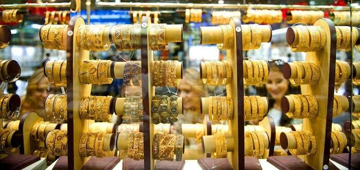 نساء يحاولن المجوهرات الذهبية المختلفة خلال مهرجان دبي للتسوق 2016