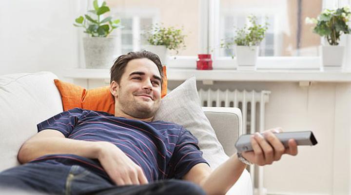 الرجل يرقد على الأريكة يشاهد التلفاز